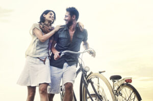 happy couple with bike living in one of the top countries for finding happiness